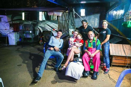 """São Paulo 25/02/2016 Athos Silva Miranda, palhaço """"Chumbrega"""", com a familia   FOTO PAULO PINTO/FOTOS PUBLICAS  ...um dia vou deixar o circo, mas o circo  jamais sairá de dentro de mim. Assim Athos Silva Miranda, ou Chumbrega, externa o seu íntimo desejo. Athos aos 73 anos , é a terceira geração de artista circense, cuja origem vem de avós romenos e austríacos, ou seja, trás no sangue a estirpe  de uma família que nasceu para o espetáculo, para levar alegria e entretenimento de norte a sul , de leste a oeste, viajar pelo mundo. Desde o trapézio ao malabarismo onde começou sua trajetória, Athos com o tempo transformou-se no palhaço """"Chumbrega"""", aquele que faz rir, que faz cada um sentir-se criança, com sorriso aberto, franco, descontraído. Hoje no circo Stankovich, a família de Athos já está na quinta geração de artistas, seus filhos e netos já se incorporaram ao picadeiro, os netos ainda timidamente, mas com sangue e alma circense esse legado vai se perpetuando. O Palhaço segundo Athos (Chumbrega) é o agente da alegria do entretenimento, do bom humor. Fazer palhaçada é para aqueles profissionais que dedicam  uma  vida a essa arte, essa mesma arte, que os torna conscientes de seu trabalho, é de onde sai o seu sustento, o picadeiro. Esse mesmo picadeiro que não aceita rancores, dores, lamentos. Esse picadeiro só cobra uma coisa desse artista, alegria, e não alegria contida, e sim a  alegria compartilhada. A vida de um artista de circo nem sempre é colorida,  mas embaixo da lona no  picadeiro as cores aparecem, brilham, e essa é a mágica do palhaço do ator. Um livro só é bom quando você consegue ler e os ensinamentos  que ele contém, você consegue passar aos outros e assim ele se multiplica, se dissemina.   """"...sou criança, sou vida, sou o instante de alegria que todos querem partilhar. Sou poeta sou cantor, sou sorriso e sou ator. Sou delas um pedaço, sou para elas um simples palhaço. Esse é """"Chumbrega"""" ou melhor,"""